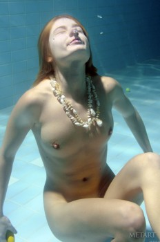 A redhead is dipping in the swimming pool