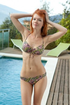 Ginger hottie poses naked at an outdoor pool.