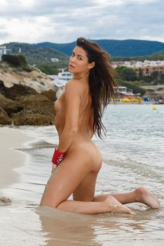 Thin girl with long hair is naked on the beach