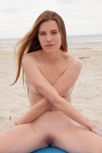 Naked babe performs yoga exercises on an empty beach