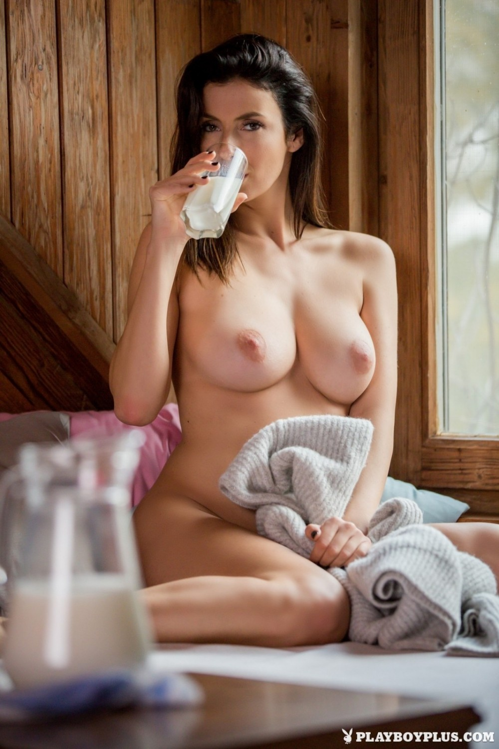 Dark-haired babe drinks milk and masturbates at once